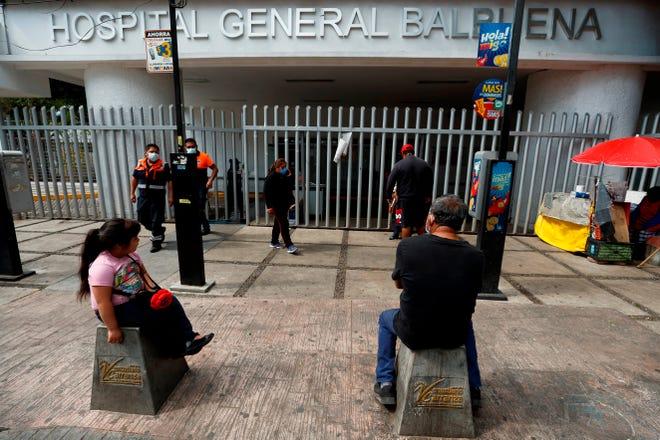 Personas esperan a las afueras del Hospital General Balbuena por información de familiares enfermos de la COVID-19, hoy en Ciudad de México.