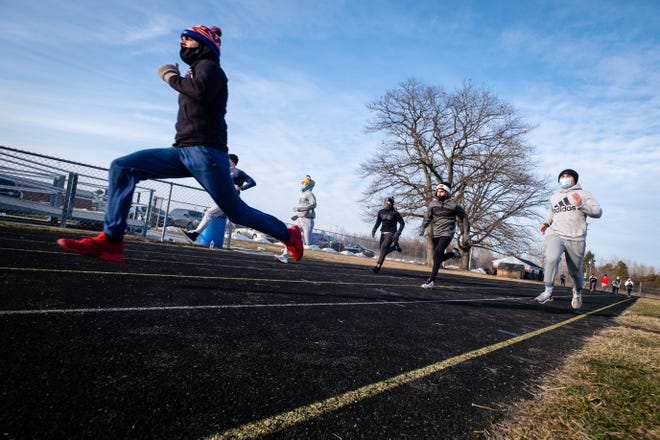 Members of the Cardinal Mooney basketball team run during the team's second track week Wednesday, Jan. 13, 2021, at Marine City High School. The team held a second track week this year due to COVID-19.