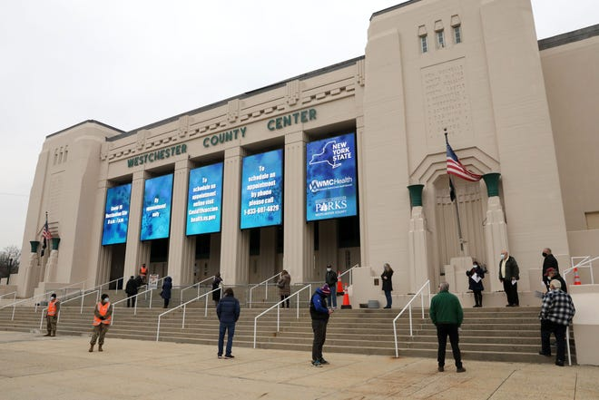 People with appointments for the COVID-19 vaccine wait on line at the Westchester County Center, one of the three mass COVID-19 vaccination sites that opened in New York state today, Jan. 13, 2021 in White Plains.