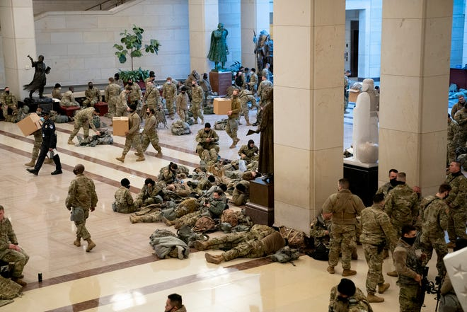 Members of the National Guard rest in the Visitor Center of the U.S. Capitol on Wednesday.