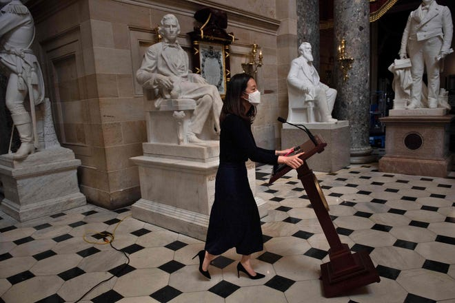 A staff member moves Speaker of the House Nancy Pelosi's lectern which was stolen as a pro-Trump mob took over the Capitol building last week January 13, 2021, in Washington, DC.
