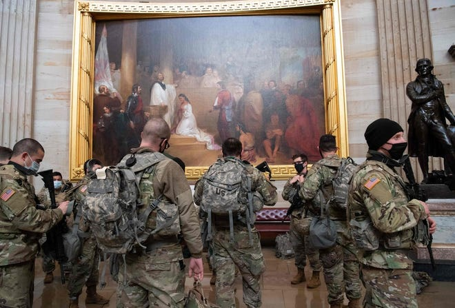 Members of the National Guard walk through the Rotunda of the U.S. Capitol.