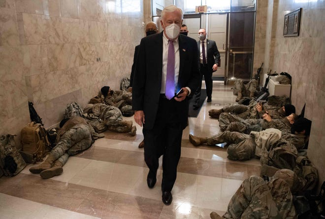 House Majority Leader Steny Hoyer, D-Md., walks past members of the National Guard as he arrives at the US Capitol in Washington, D.C., on Wednesday, when the House plans to vote to impeach President Donald Trump a second time.