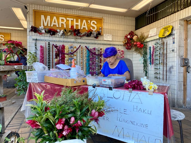 Milan Chun selects flowers for a lei as she waits for customers at her shop near Honolulu's Daniel K. Inouye International airport.