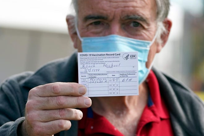 Dr. Michael Roach shows his vaccination card on Wednesday after receiving the Moderna COVID-19 vaccine at a site for health care workers in Pacoima, Calif.