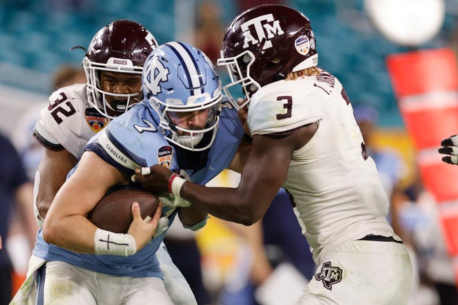 Texas A&M defenders Tyree Johnson (3) and Andre White Jr. sack North Carolina quarterback Sam Howell  during the fourth quarter of the 2021 Orange Bowl at Hard Rock Stadium in Miami Gardens, Florida.