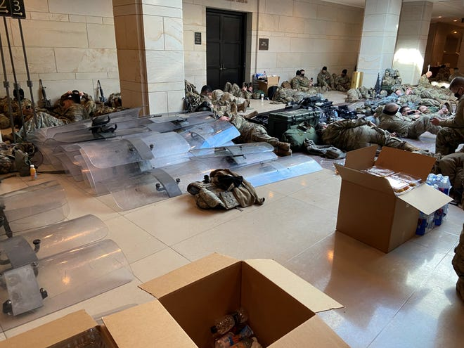 Riot shields are seen stockpiled in the Capitol as Guard members rest on Wednesday.