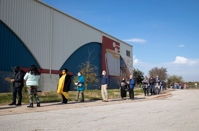 People wait in line for the coronavirus vaccine at an Austin distribution site on Jan. 12. Employers and employees alike are dealing with uncertainty caused in part by the vaccine's uneven rollout.