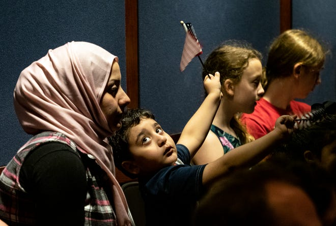 Ali Alyourany, 4, looks back at his mother, Rafah Alyourany, as his father, Salah Alyourany, originally from Iraq, is sworn in during the U.S. Naturalization Ceremony. The event was part of World Refugee Day at the Bullock Texas State Museum in 2019 in Austin. [Rodolfo Gonzalez/ for American-Statesman]
