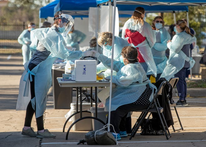 Nurses from Ascension Seton and the Austin school district's student health services office take a sample at a drive-thru COVID-19 testing site at AISD Central Office on Thursday.