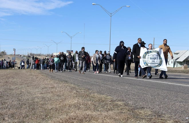 Individuals participate in a march on Martin Luther King Jr. Day in 2019