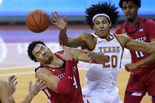 Texas Tech's Marcus Santos-Silva (14) and Texas' Jericho Sims (20) compete for a rebound.