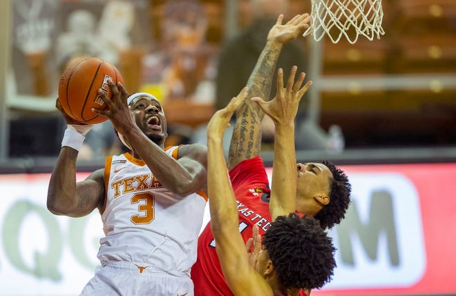Texas guard Courtney Ramey drives and shoots over Texas Tech guards Kyler Edwards, center, and Micah Peavy during Wednesday night's loss to the Red Raiders at the Erwin Center.