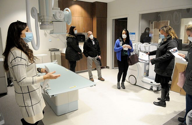 OhioHealth director of care management Chelsea Zigan, right, talks with Joe Abraham from LSS The Good Shepherd, third from right, inside the radiology room as he and his staff toured the new OhioHealth Ashand Health Center on Wednesday. It will open at the end of January. TOM E. PUSKAR/TIMES-GAZETTE.COM