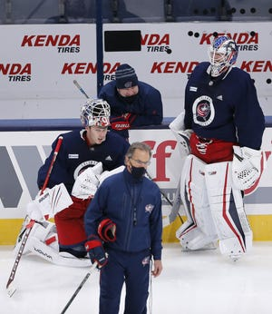 Everyone was wearing a mask of some sort when Blue Jackets coach John Tortorella, front, and goaltending coach Manny Legace conferred at a recent practice with goalies Elvis Merzlikins, left, and Joonas Korpisalo.