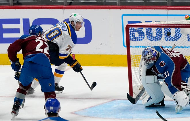 St. Louis Blues center Oskar Sundqvist, back, drives past Colorado Avalanche defenseman Conor Timmins, left, to score a goal against goaltender Philipp Grubauer in the third period Wednesday in Denver. The Blues won 4-1.