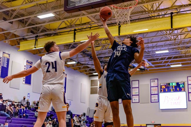 Tolton's Jevon Porter (14) scores a layup through the defense of Hickman's Seth Larson (24) and TJ Turner (15) during a game Wednesday night at Hickman High School.