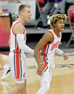 Ohio State Buckeyes guard Meechie Johnson Jr. (0) celebrates with Ohio State Buckeyes forward Justin Ahrens (10) after making a three-point basket during the first half of Wednesday's NCAA Division I basketball game against the Northwestern Wildcats at Value City Arena in Columbus, Oh., on Wednesday, January 13, 2021.