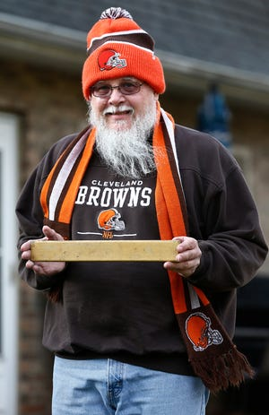 Ralph Mausser, who has had Browns season tickets since 1969, holds a slat from his old seat at Cleveland Municipal Stadium. He grew up in Cleveland and moved to Delaware County in 1990 for work, but still went to every home game for years. He opted out of his season tickets this year because of the pandemic but has still watched at home.