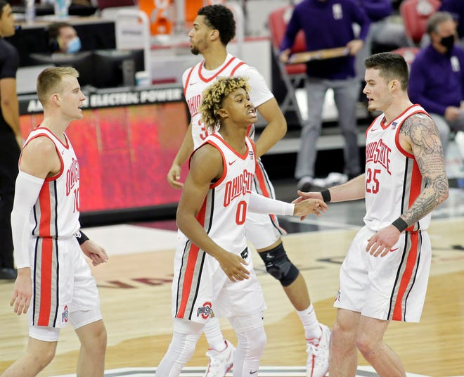 Ohio State Buckeyes guard Meechie Johnson Jr. (0) celebrates with Ohio State Buckeyes forward Justin Ahrens (10) and Ohio State Buckeyes forward Kyle Young (25) after making a three-point basket during the first half of Wednesday's NCAA Division I basketball game against the Northwestern Wildcats at Value City Arena in Columbus, Oh., on Wednesday, January 13, 2021.