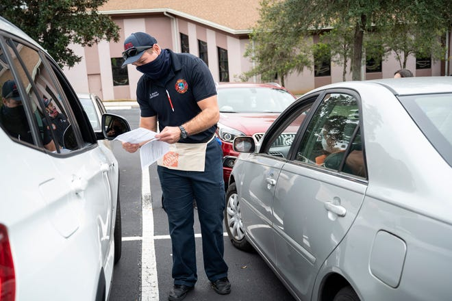 A Mount Dora firefighter goes over information on the Covid-19 vaccine shot as people wait for their vaccine in Mount Dora on Wenesday. [Cindy Peterson/Correspondent]