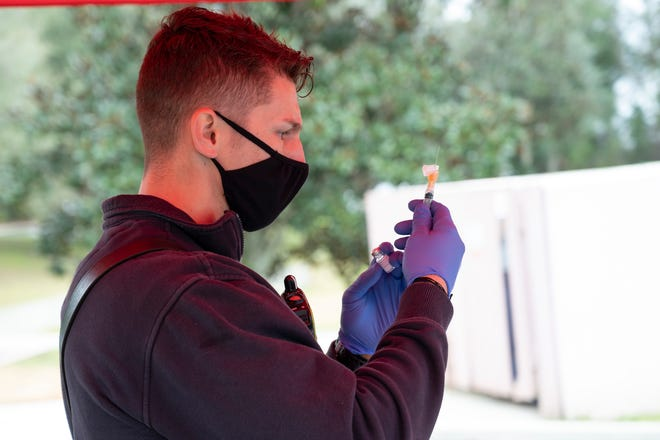 A Mount Dora firefighter prepares Covid-19 a vaccine shot to administer in Mount Dora on Wenesday. [Cindy Peterson/Correspondent]