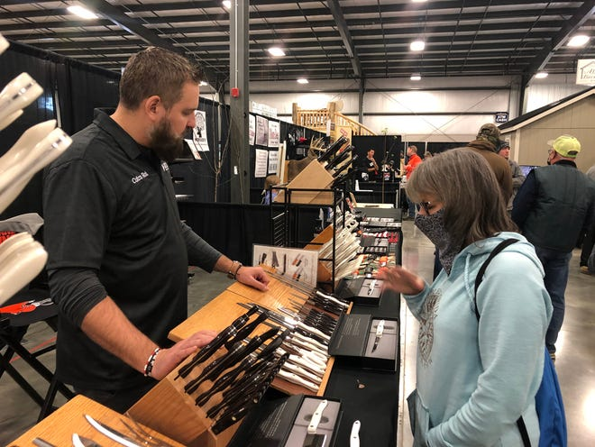 Rob Robincheck of Cutco Rob and Helen Mullett talk kitchen cutlery at one of the display booths at the Northeast Ohio Sportsman Show on Friday.