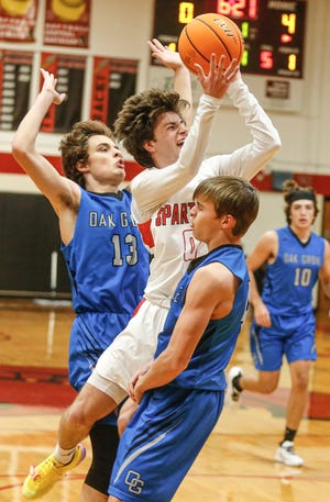 Central Davidson's Dylan Tysinger takes a shot in front of Oak Grove's Noah Richey as Oak Grove's Max Hester (right) tries to draw a charging foul on Tysinger during the 2019-20 season. The Spartans beat Western Guilford on Wednesday. [Michael Coppley for The Dispatch]