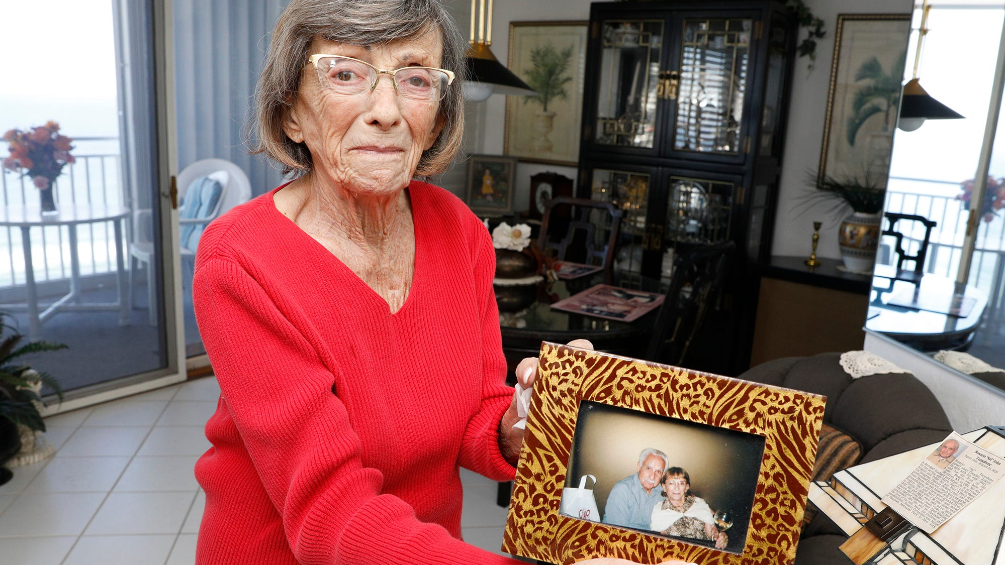 """Mary Tornabene, 92, shows a photo of her and her late husband, Sal, who died in August at age 96. She desperately wants to get the COVID vaccine so she can feel safe traveling to visit her only remaining family in New York. """"I won't go without a shot,"""" she said. """"It would put my life in danger and it would put others' lives in danger."""""""