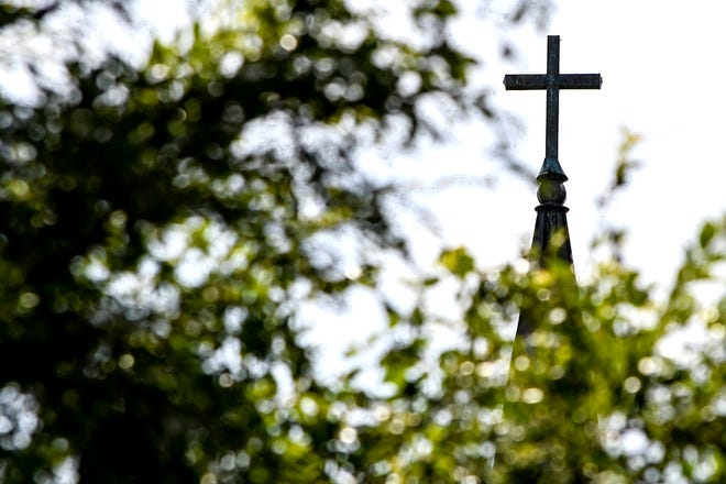 A cross sits atop a church in this file photo