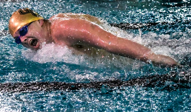 Garden City High School's Connor Cupp comes up for a breath as he makes a stroke in the 100-yard butterfly in December 2019 during a home triangular at the Garden City Family YMCA.