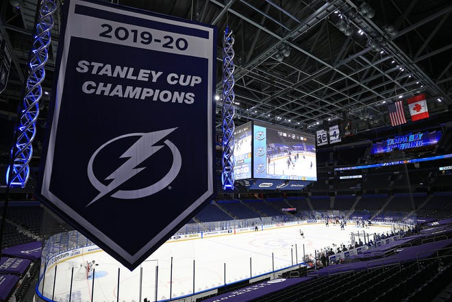 The Tampa Bay Lightning raise the banner celebrating winning the Stanley Cup for the 2019-20 NHL season during a game against the Chicago Blackhawks on opening night of the 2020-21 NHL season  at Amalie Arena on Wednesday, Jan. 13, 2021, in Tampa, Fla.