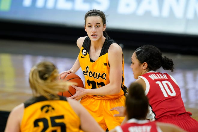 Iowa guard Caitlin Clark, center, looks to pass the ball during the first half of the team's game against Ohio State on Wednesday, Jan. 13, in Iowa City, Iowa.