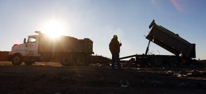 A Reno County landfill worker directs a truck as it unloads in this file photo.