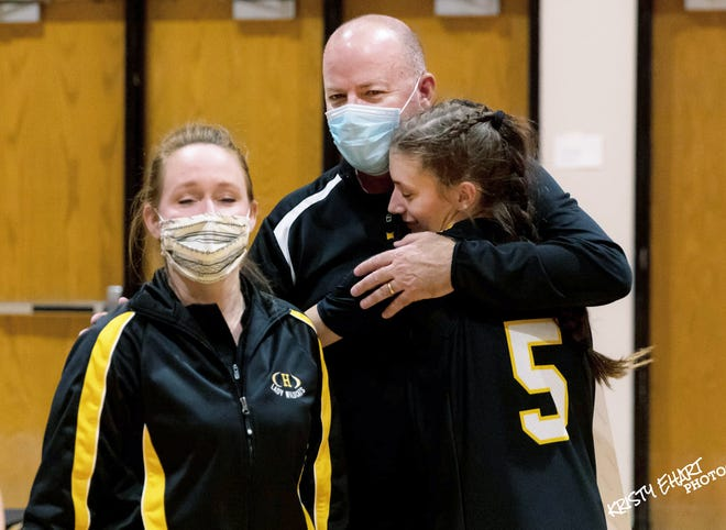Dwight Roper hugs his daughter, Reese Roper, with assistant coach Tara Cooprider, left, at the conclusion of his 500th career basketball game win against Larned on Tuesday evening.
