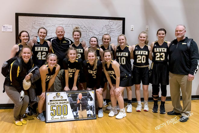 Head coach Dwight Roper, left, is surrounded by his players and assistant coaches after his 500th career win as the Haven girls basketball team won their game 50-19 on Tuesday night against Larned.
