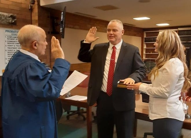 New Massillon City Councilman Jamie Slutz, R-at large, (center) was sworn into office Thursday morning by Municipal Judge Edward Elum (left) in a municipal courtroom. Slutz was joined by his wife, Christie.