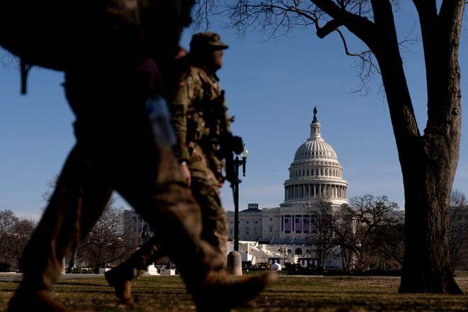 Members of the National Guard walk past the dome of the Capitol Building on Capitol Hill in Washington, D.C., on Thursday. [AP Photo/Andrew Harnik]