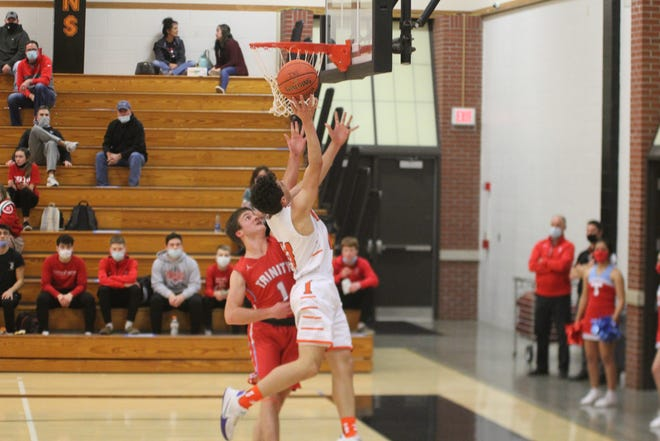 Inman's Tanner Heckel shoots a layup over Trinity's Blake Hammeke during Tuesday's game. Trinity defeated Inman 54-39.