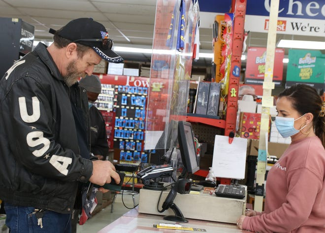 A customer gets out his money to give to Samantha Davis at Lester's Hardware Thursday, Jan. 14.