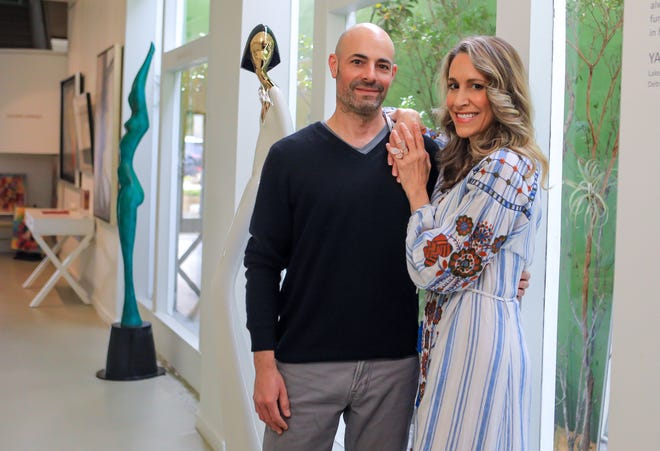Haven Palm Beach owners and Anthony Burroughs and Stephanie Kantis stand Wednesday inside their gallery, which they opened just before Thanksgiving.  David Hostetler sculptures are in the background.