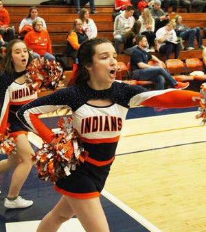 Two members of the Pontiac Township High School cheerleading squad cheer during a boys' basketball game last season. Cheerleaders might be able to take part in competitive cheer later in this winter sports calendar, but basketball will have to wait.