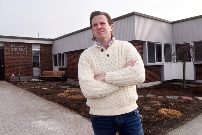 """Portsmouth City Councilor Deaglan McEachern stands in front of New Franklin, one of the city's elementary schools. McEachern has been vocal about the floated possible return to a """"donor town"""" education funding system, which would have the property-rich city send its taxpayer money to other communities."""