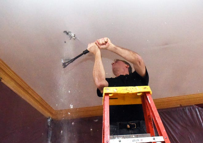 Herman Ejarque, co-owner of the Governor's Inn, works on a 100-year-old ceiling, as part of the renovation of the main dining room.