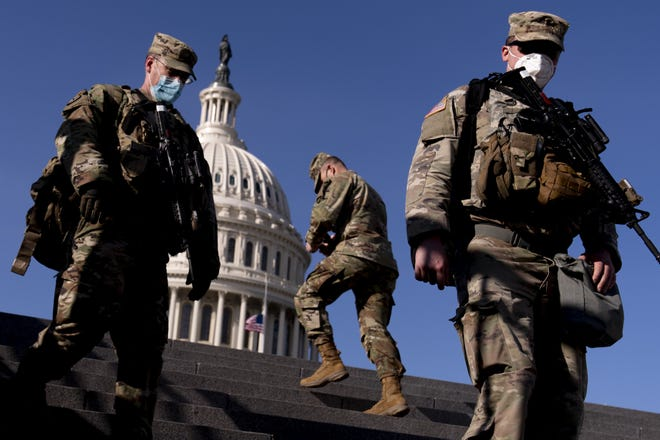 Members of the National Guard walk past the Dome of the Capitol Building on Capitol Hill Thursday in Washington. ANDREW HARNIK/Assocaited Press