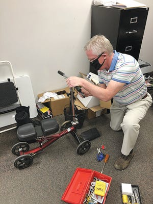 Terry Gatlin works on a knee scooter for a patient at Gatlin Pharmacy in Pratt. Gatlin Pharmacy has also started carrying an increased number of walkers and other related assistive devices.