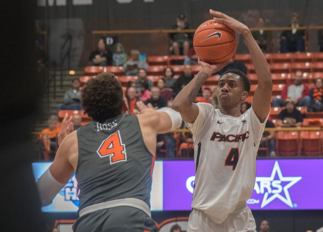 Pacific's Daniss Jenkins, right, shoots from 3-point range over Pepperdine's Colbey Ross during a WCC men's basketball game Feb. 8 at Spanos Center in Stockton.