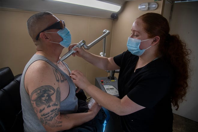 Registered nurse Elizabeth Aguilar with Inkoff.me, right, uses a laser to remove tattoos from Freddy Rubio's chest at a tattoo removal event in a lot next to the Fathers & Families of San Joaquin's Brandon Harrison Memorial Garden in downtown Stockton. The free event aims to help formerly incarcerated people find jobs.