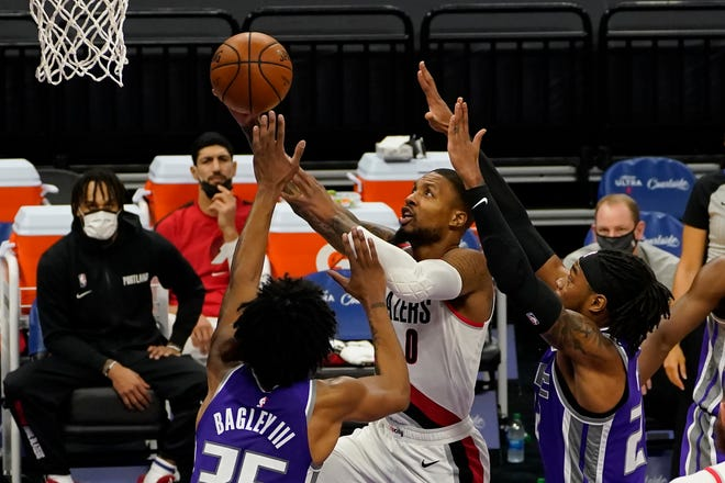 Portland's Damian Lillard drives to the basket against Sacramento's Marvin Bagley III, left, and Richaun Holmes during Wednesday's game in Sacramento.