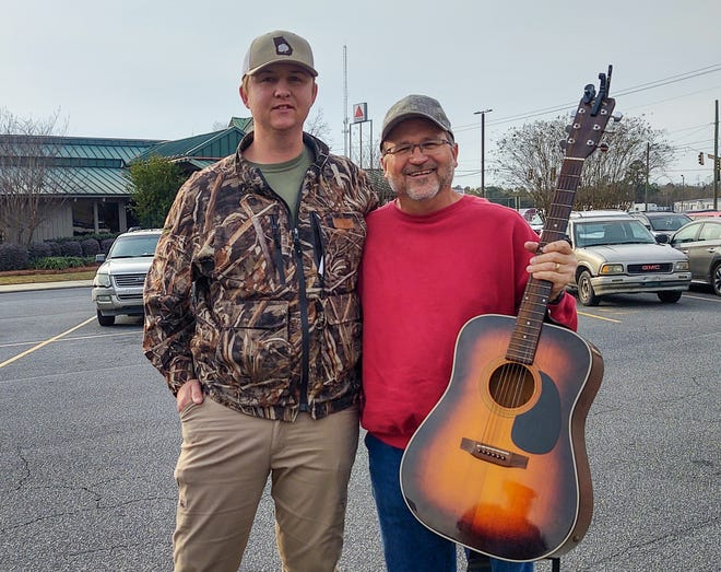 Jake Perry, on left, from Ashburn, Georgia, who found the guitar in nearby Tifton, Georgia, that he and his family eventually returned to owner Andy Dickson, of Ponte Vedra Beach.